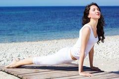 Girl doing yoga exercises on the sea coast Stock Images