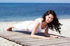 Girl doing yoga exercises on the sea coast Royalty Free Stock Photo