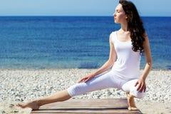 Girl doing yoga exercises on the sea coast Stock Photo