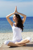 Girl doing yoga exercises on the sea coast Stock Image