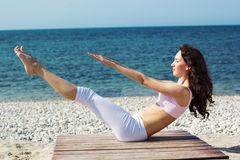 Girl doing yoga exercises on the sea coast Stock Images