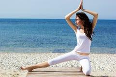 Girl doing yoga exercises on the sea coast Stock Photography