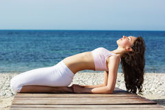Girl doing yoga exercises on the sea coast Royalty Free Stock Images