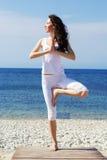 Girl doing yoga exercises on the sea coast Royalty Free Stock Photos