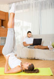 Girl doing yoga and man with laptop. Girl doing asana at home and her boyfriend resting on couch with laptop Royalty Free Stock Photos