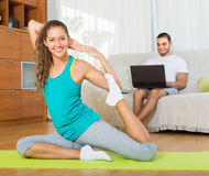 Girl doing yoga and man with laptop Royalty Free Stock Image
