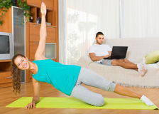 Girl doing yoga and man with laptop Royalty Free Stock Photos