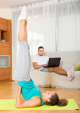 Girl doing yoga and man with laptop. Young girl doing yoga at home and her boyfriend resting on couch with laptop Royalty Free Stock Images