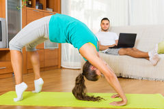 Girl doing yoga and man with laptop Stock Photography