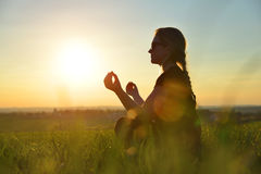 Girl doing yoga. On meadow at sunset Stock Images
