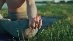 Girl doing yoga in morning at lake. Hands of woman in lotus position at sunrise stock video footage