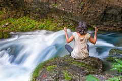 A girl doing yoga near the birth of a river from the rock Stock Photography