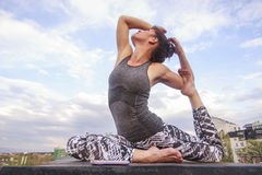 Girl doing yoga outdoors.(YOGICHICKS) Stock Photo