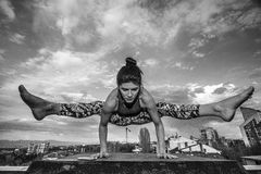 Girl doing yoga outdoors. Maya Bahchevanska doing yoga on the roof on the background of a big city and the blue sky Stock Photos