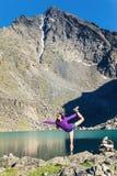 Girl doing yoga pose on a mountain lake Stock Photography