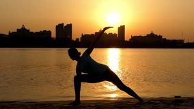 Girl Doing the Yoga Pose Triangle. Sunset. stock footage