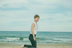 Girl doing yoga poses on the beach. Practicing a healthy lifestyle Royalty Free Stock Images