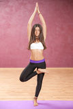Girl doing yoga posture standing on one leg. With closed eyes Stock Photos