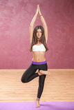 Girl doing yoga posture standing on one leg. With open eyes Stock Photos