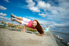 Girl doing yoga on the roof. Woman doing handstand fitness blue sky background Royalty Free Stock Image