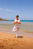 Girl doing yoga. On a sandy beach Stock Photography