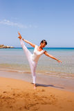 Girl doing yoga. On a sandy beach Royalty Free Stock Photography