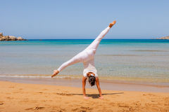 Girl doing yoga. On a sandy beach Royalty Free Stock Photos