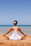 Girl doing yoga. On a sandy beach stock photo