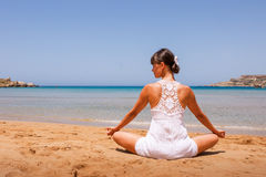 Girl doing yoga. On a sandy beach Royalty Free Stock Image