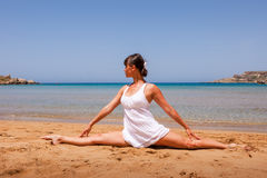 Girl doing yoga. On a sandy beach Stock Image