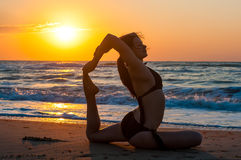Girl is doing yoga, sitting in One-Legged King Pigeon pose, Eka Pada Rajakapotasana on  beach with first ray of sunshine Royalty Free Stock Images
