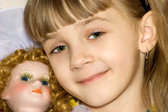 The girl with a doll. The girl has nestled on a doll and smiles Royalty Free Stock Photography