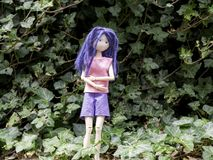 Girl doll alone in the forest afraid and cold stock photo