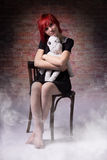 Girl with a doll on chair in the fog Stock Photo