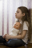 Girl With Doll Sitting At Home Stock Image