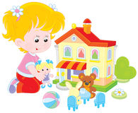 Girl with a doll and toy house. Little girl playing with a small doll, bear, rabbit and toy house Stock Photo