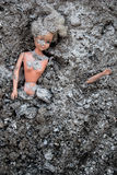 Girl doll toy lying in the pile of ash Stock Photography