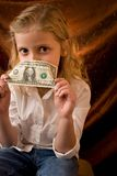 Girl with dollar. Little girl holding a one dollar bill Royalty Free Stock Images
