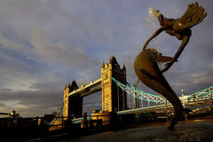 Girl with a Dolphin. Situated on the north bank of the Thames 'Girl with a Dolphin' was created by artist David Wynne in 1973. In the background is Tower Bridge Stock Photography