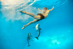 Girl with dolphin. Girl swimming underwater near the dolphins Stock Image