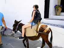 Girl on donkey with guide Royalty Free Stock Photos