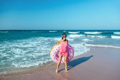 Girl with donut lilo on the beach. Girl relaxing with donut lilo on the beach. Playing with inflatable ring. Summer holiday idyllic on a tropical island Stock Image