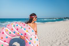 Girl with donut lilo on the beach. Girl relaxing with donut lilo on the beach. Playing with inflatable ring. Summer holiday idyllic on a tropical island Stock Photos