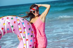 Girl with donut lilo on the beach. Girl relaxing with donut lilo on the beach. Playing with inflatable ring. Summer holiday idyllic on a tropical island Stock Photo
