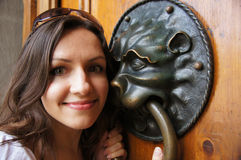 Girl with Door knocker. Young white female compares faces with a door knocker. Taken in Switzerland royalty free stock images
