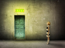 Girl door room exit sign. Young woman in black and white dress stand in front of blue door in dark grungy room watch on glowing exit sign - find the way out royalty free stock photos