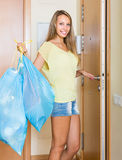 Girl at the door with trash bags Royalty Free Stock Photography