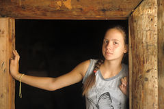 Girl in the doorway of a wooden hut Stock Photo