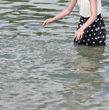 Girl with dotted dress splashing water Stock Images