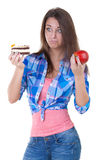 Girl in doubt with an apple and a cake Royalty Free Stock Image